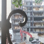 Photo of dozer captured through wrought-iron scroll at demolition of 3400 Montrose, 2014